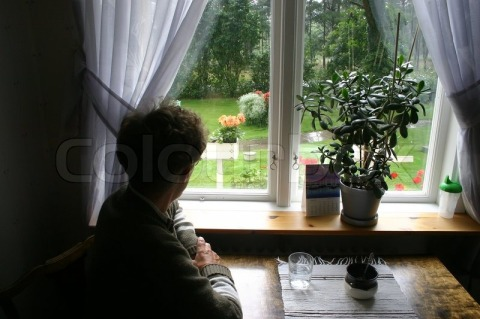 1184268-an-old-lonely-lady-sitting-next-to-her-kitchen-table-looks-out-of-her-window-it-is-raining-outside-horizontal-picture
