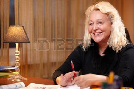 19203123-english-teacher-sitting-at-the-table-and-smiling-to-the-camera