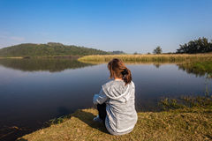 girl-sitting-banks-river-lagoon-young-grass-bank-looking-over-smooth-glass-waters-vegetation-32086374